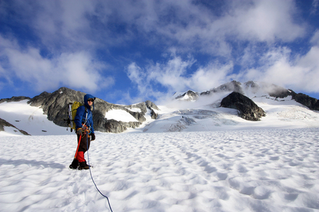 Mountaineer climbing up the Wedgemount Glacier in Garibaldi Provincial Park of British Columbia, Canada. Wedge Mountain the highest summit in the park in the background.