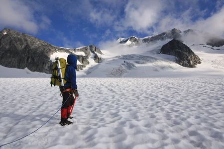 Mountaineer crossing the Wedgemount Glacier in Garibaldi Park of British Columbia, Canada. Wedge Mountain the highest peak in the park in the background. Stock Photo