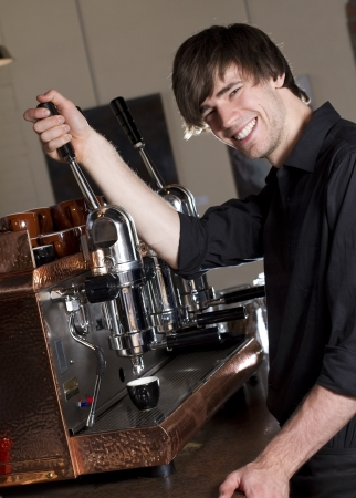 Barista making an espresso  a barista smiles at the camera while brewing an espresso working in a cafe  photo