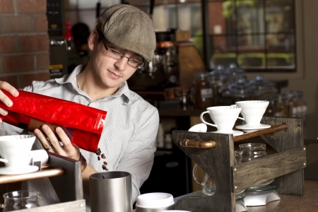 Pouring Beans Left  a cafe employee pours fresh coffee beans into grinder  focus on beans 写真素材