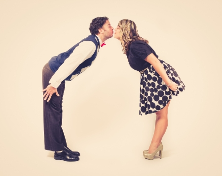 Lean in Kissing Retro  A young male and young female lean in to kiss each other  Retro feel against a clean backdrop  photo