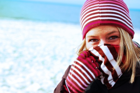 Winter Girl Bundled a close up shot of a girl bundled up in a winter hat, gloves and scarf outside against a snowy background  lively colors and stripes  photo