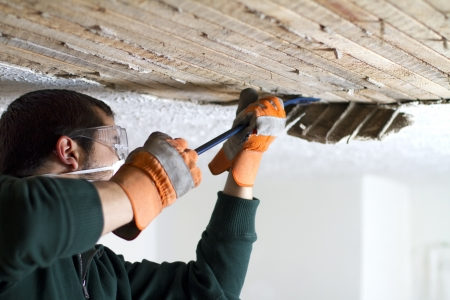 ceiling: Ceiling Scrape man scraping plaster off of ceiling lathe with a crowbar