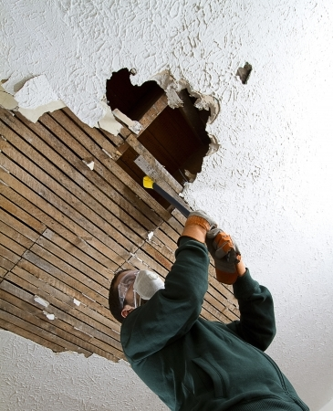 Ceiling Take Down vertical shot from below of a man pulling down plaster ceiling lathe with a crowbar  large hole in ceiling