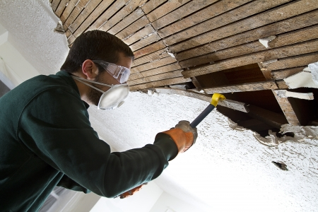 Ceiling Demolition man removing plaster lathe from ceiling with a crowbar photo