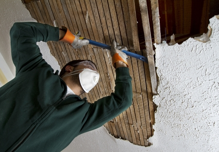 Ceiling Repair man removing plaster lathe from ceiling  view from below   photo