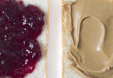 peanut butter and jelly: Jelly vs Peanut Butter side by side shot  slice of bread with grape jelly and a slice with creamy peanut butter  Stock Photo