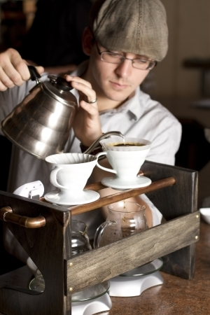 a barista brews a single cup of coffee using a unique method and traditional style  the hot water drips through the filter and grinded beans above into glass mugs  focus on contraption
