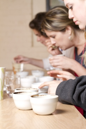 three women taste and compare brewed coffees at a cafe  Process is known as Coffee Cupping  focus is on coffee crusted cups