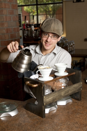 brewing: a barista smiles at the camera while brewing a special cup of coffee