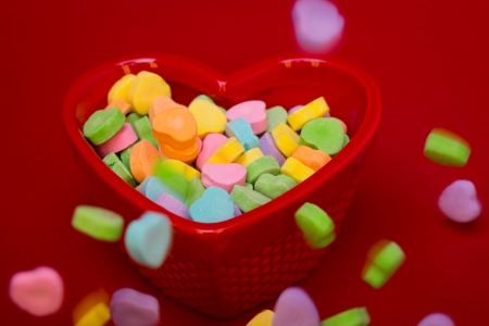 heart candies fall around a heart shaped cand dish on a red textured background  photo