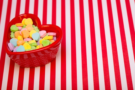 justified: a heart shaped candy dish filled with heart candies left justified on a red and white striped background  copyspace