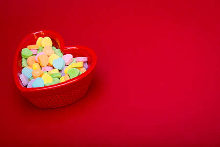 justified: a heart shaped candy dish filled with heart candies left justified on a red textured background  copyspace Stock Photo