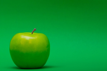 justified: a left justified plastic green apple on a green background  Stock Photo