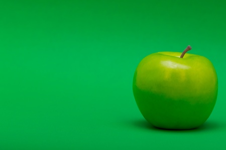 justified: a right justified plastic green apple on a green background  copyspace Stock Photo