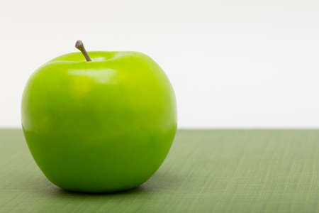 justified: a left justified plastic green apple on patterned ground with a white background  copyspace