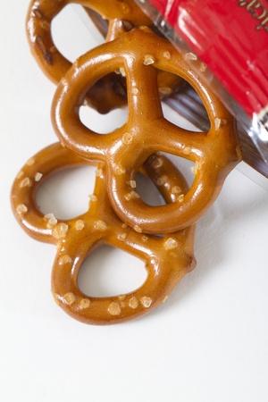 pretzels: pretzels fall out of bag with white back drop