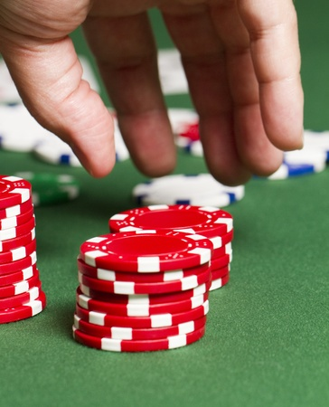 a close up as a hand moves in to grab some red poker chips on a poker table