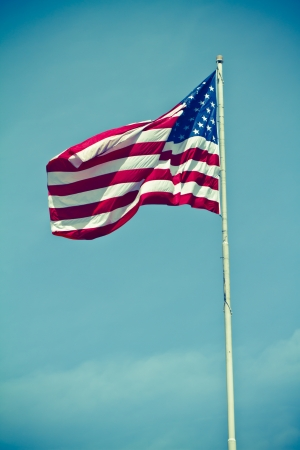 a vintage style photo of the american flag waving on a pole with a vignette against a blue sky.  photo