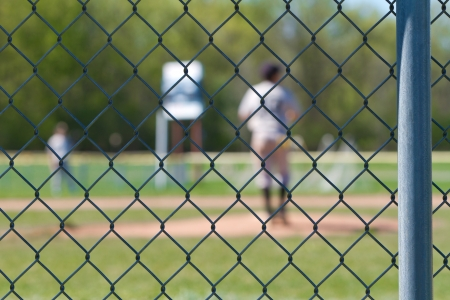 a chain link baseball fence with a blurred out backdrop of a baseball game going on.  photo