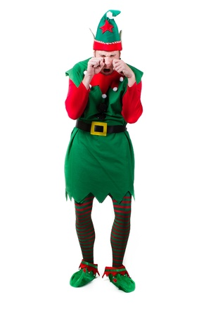 christmas costume: a full body shot of a male elf rubbing his eyes crying and upset. shot on white.