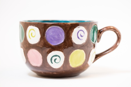 crafted: a macro selective shot of a hand painted mug in a studio. focus on side of mug