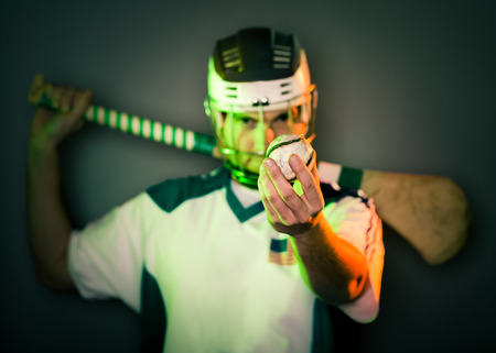 a hurling player holds a ball in front of his face holding the stick on his shoulders  shallow depth of field  green and orange light  focus on ball,