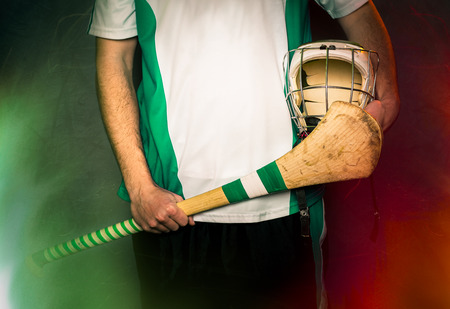 gaelic: mid section of a hurling player holding a hurling stick and helmet