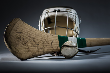 a studio shot of a hurling stick, ball, and helmet
