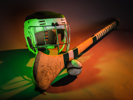 Hurling Ball Close Up  a studio shot of a hurling stick, ball, and helmet in colorful green and orange light  irish 写真素材