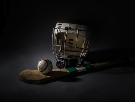 Hurling Equipment From Above  a studio shot of a hurling stick, ball, and helmet  single light illumination