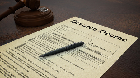 divorce court: Side low shot of a divorce decree paper with a pen, gavel and rings in the scene Stock Photo
