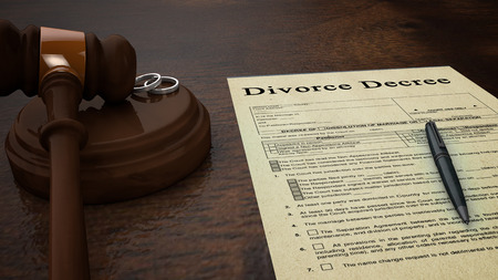 Front low shot of a divorce decree paper with a pen, gavel and rings in the scene