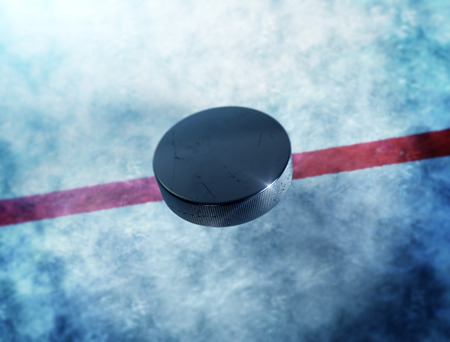 ice hockey puck: Hockey puck above the ice and red line with lens flare around puck. Stock Photo