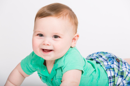 8 year old: 8 month year old baby lays on his stomach looking towards camerawith big smile. dressed in a cute green polo shirt and blue plaid shorts. Stock Photo