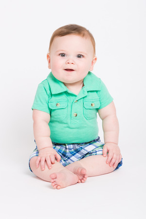 8 year old: 8 month year old baby sits on a white background smiling towards the camera. dressed in a cute green polo shirt and blue plaid shorts.