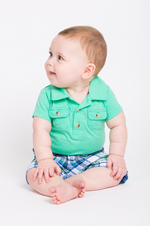 right on: 8 month year old baby sits on a white background looking off camera. dressed in a cute green polo shirt and blue plaid shorts.