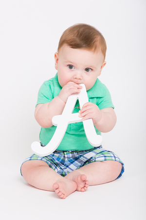 baby sitting: 8 month year old baby sits on a white background holding a white letter A to his mouth looking to the left. dressed in a cute green polo shirt and blue plaid shorts.