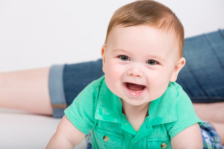toddler boy: 8 month year old baby lays on his stomach looking towards camera, while mom is sitting in background. dressed in a cute green polo shirt and blue plaid shorts.