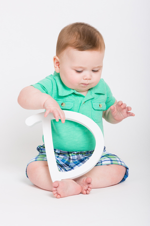 eyes looking down: 8 month year old baby sits on a white background holding a white letter D looking at floor. dressed in a cute green polo shirt and blue plaid shorts. Stock Photo