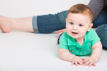 looking towards camera: 8 month year old baby lays on his stomach looking towards camera, while mom is sitting in background. dressed in a cute green polo shirt and blue plaid shorts.
