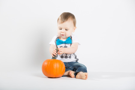 bare feet boys: a cute 1 year old sits in a white studio setting with a pumpkin. The boy looks very interested in the pumpkin.. He is dressed in Tshirt, jeans, suspenders and blue bow tie