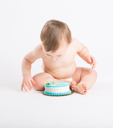 1 boy only: a cute 1 year old sits in a white studio setting. The boy is very excited to start eating his birthday cake. He is only dressed in a white diaper
