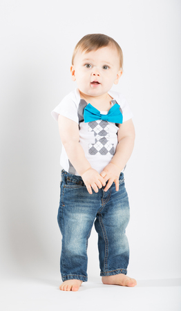 bare feet boys: a cute 1 year old stands in a white studio setting. The boy has a intent expression. He is dressed in Tshirt, jeans, suspenders and blue bow tie
