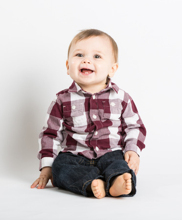 babies playing: a cute 1 year old baby sits in white studio with jeans and a red white flannel looking and laughing looking above camera