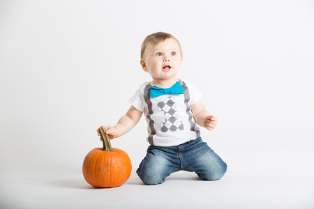 a cute 1 year old sits in a white studio setting with a pumpkin. The boy is on his knees holding pumpkin stem and looking off camera. He is dressed in Tshirt, jeans, suspenders and blue bow tie