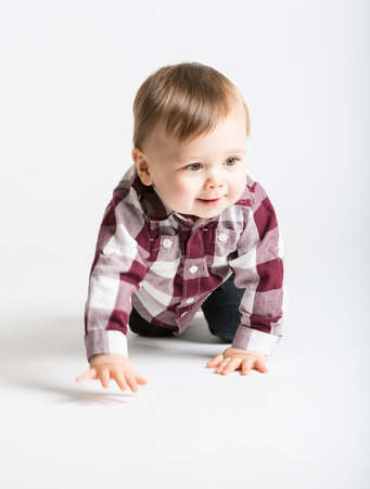 bare feet boys: a cute 1 year old baby starts to crawl toward camera in white studio with jeans and a red white flannel looking right Stock Photo