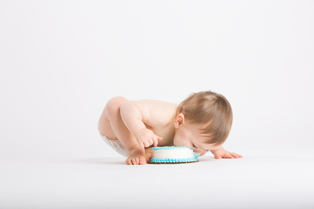 1 year old: a cute 1 year old sits in a white studio setting. The boy takes a huge bite of cake on the floor with his face.. He is only dressed in a white diaper