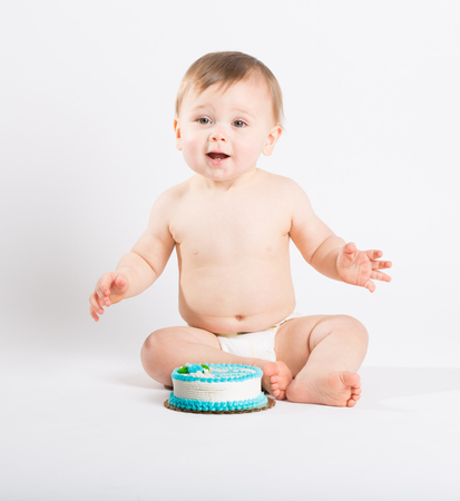 one year: a cute 1 year old sits in a white studio setting. The boy is very excited to start eating his birthday cake. He is only dressed in a white diaper