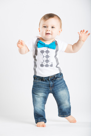 a cute 1 year old stands in a white studio setting. The boy has a happy expression with his hands out. He is dressed in Tshirt, jeans, suspenders and blue bow tie